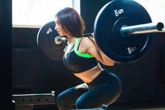 Menina apta nova que faz ocupas resistentes no gym com o barbell no sportswear bonito imagem de stock