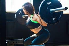 Menina apta nova que faz ocupas resistentes no gym com o barbell no sportswear bonito fotografia de stock