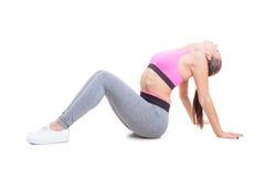 Menina apta que dobra-se sobre o esticão traseiro para o exercício Fotos de Stock