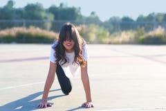 Menina apta que faz o exerc?cio da prancha exterior no dia de ver?o morno do parque fotos de stock