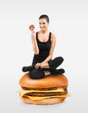 Menina apta que senta-se em um Hamburger que guarda uma maçã Foto de Stock Royalty Free
