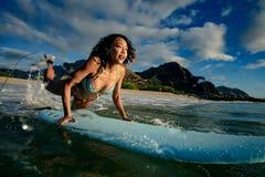 Menina apta que tem o divertimento que começa surfar na água do oceano imagem de stock
