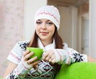 A menina aquece-se com o copo do chá na casa imagem de stock royalty free