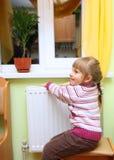 A menina aquece suas mãos perto do radiador. Fotografia de Stock
