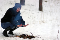 A menina aquece suas mãos sobre o fogo no inverno Imagens de Stock Royalty Free