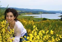 A menina, as flores do amarelo e o lago Imagens de Stock Royalty Free