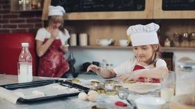 Menina ascendente próxima que tem o divertimento ao fazer um daugh para cookies na sala da cozinha Tiro do retrato indoor vídeos de arquivo
