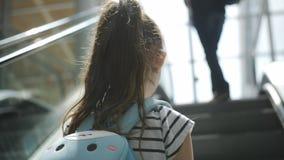 Menina ascensão na escada rolante ao assoalho seguinte no terminal de aeroporto