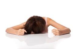A menina asiática é deprimida, doente, enfrenta abaixo da tabela imagens de stock royalty free