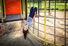 A menina asiática é pendurar de cabeça para baixo em um campo de jogos exterior e olhar a câmera no parque, verão, conceito das f fotografia de stock