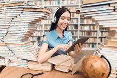 Menina asiática étnica cercada por livros na biblioteca O estudante está usando a tabuleta imagens de stock