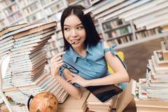 Menina asiática étnica cercada por livros na biblioteca O estudante está usando a tabuleta fotografia de stock royalty free
