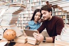 Menina asiática étnica e indivíduo branco cercados por livros na biblioteca Os estudantes estão usando a tabuleta imagem de stock