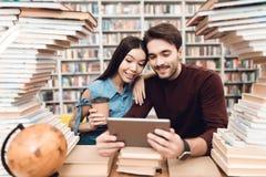 Menina asiática étnica e indivíduo branco cercados por livros na biblioteca Os estudantes estão usando a tabuleta fotografia de stock