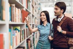 Menina asiática étnica e indivíduo branco na biblioteca Os estudantes estão procurando livros imagens de stock
