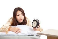 A menina asiática acorda o olhar atrasado no despertador Imagem de Stock Royalty Free