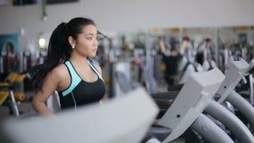 Menina asiática atrativa que corre na escada rolante no gym Cara direita do perfil filme