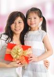 Menina asiática que dá um presente a sua mãe feliz fotos de stock