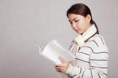 A menina asiática bonita com lenço leu um livro Imagens de Stock