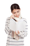 A menina asiática bonita com lenço leu um livro triste Fotografia de Stock Royalty Free