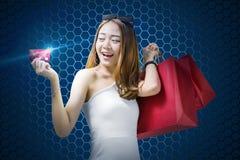 Menina asiática bonita com os sacos de compras que mostram seu cartão de crédito fotos de stock
