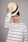 A menina asiática bonita decola um chapéu Imagem de Stock