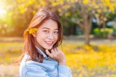 Menina asiática bonita do jovem adolescente com a flor do amarelo da natureza fotografia de stock royalty free