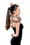 Menina asiática bonita em pouco vestido preto que guarda uma serpente Fotografia de Stock Royalty Free