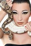 Menina asiática bonita em pouco vestido preto que guarda uma serpente Foto de Stock Royalty Free