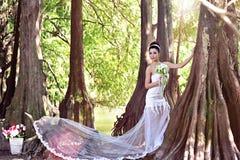 Menina asiática bonita em um vestido de casamento que mostra momentos felizes imagens de stock