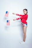 Menina asiática bonita no equipamento patriótico que mantém bandeiras americanas isoladas no branco Foto de Stock