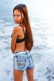 Menina asiática bonita nova que está na água na praia Imagem de Stock