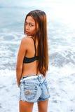Menina asiática bonita nova que está na água na praia Fotografia de Stock Royalty Free