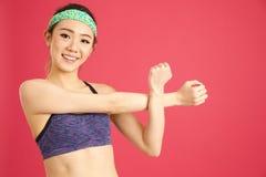 Menina asiática bonita que estica enquanto fazendo a ginástica aeróbica e a ioga na Imagens de Stock
