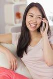 Menina asiática bonita que fala em seu smartphone no sofá Imagens de Stock Royalty Free