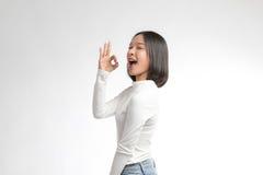 Menina asiática bonita que faz o sinal APROVADO foto de stock royalty free