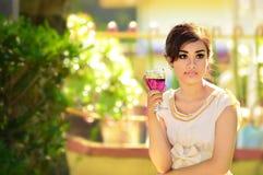Menina asiática bonita que guarda um vidro do vinho no partido de noite imagens de stock royalty free