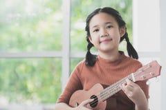 Menina asiática bonita que joga a uquelele imagens de stock royalty free