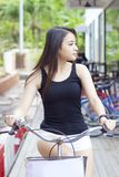 Menina asiática bonita que monta uma bicicleta Foto de Stock