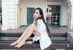 Menina asiática bonita que senta-se em um banco público imagem de stock