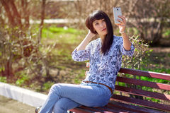 Menina asiática bonita que senta-se no banco no parque, fazendo o selfie no smartphone Imagens de Stock Royalty Free
