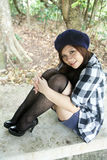Menina asiática bonita que senta-se para baixo Imagem de Stock