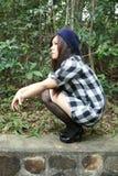 Menina asiática bonita que squatting Imagem de Stock