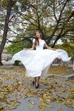 A menina asiática bonita vestiu-se em uma vibração branca da saia do vestido Fotografia de Stock Royalty Free