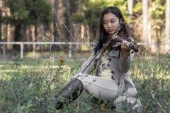 Menina asiática bonito com um violino imagens de stock