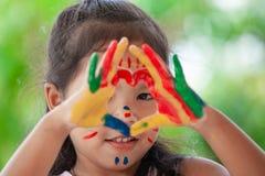 A menina asiática bonito da criança pequena com mãos pintadas faz a forma do coração Foto de Stock