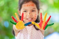 Menina asiática bonito da criança pequena com mãos pintadas que sorri com divertimento Fotografia de Stock