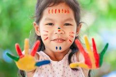 Menina asiática bonito da criança pequena com mãos pintadas que sorri com divertimento Fotografia de Stock Royalty Free
