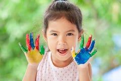 Menina asiática bonito da criança pequena com mãos pintadas que sorri com divertimento Fotos de Stock Royalty Free