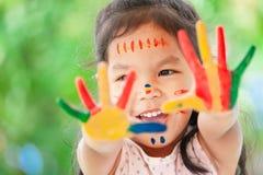 Menina asiática bonito da criança pequena com mãos pintadas que sorri com divertimento Foto de Stock Royalty Free